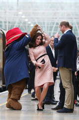 Britain's Prince William watches as his wife Catherine the Duchess of Cambridge dances with a costumed figure of Paddington bear on platform 1 at Paddington Station, as they attend the Charities Forum in London