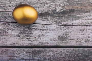Background of Golden egg on a wooden surface