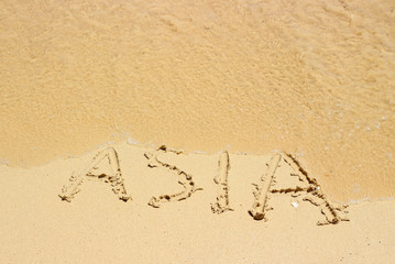 Sea wave erases the inscription Asia on the wet sand on the tropical beach.