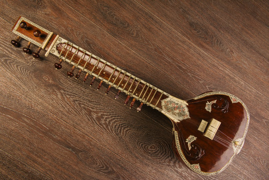 Indian musical instrument sitar lying on the wooden floor