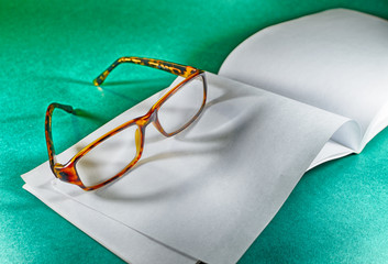 glasses on the book.On the table are glasses,for vision correction.