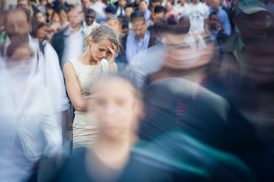 Depressed young woman feeling alone amid a crowd of people in a big city