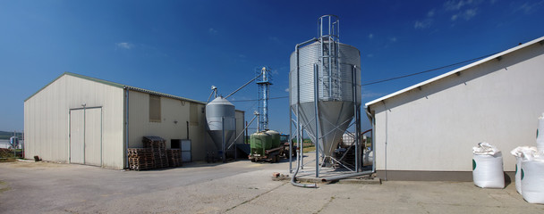 Modern farm buildings with silos and tractor