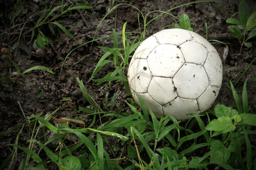 Old soccer ball in the grass.