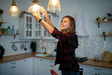 Young happy woman twists a light bulb in the kitchen lamp
