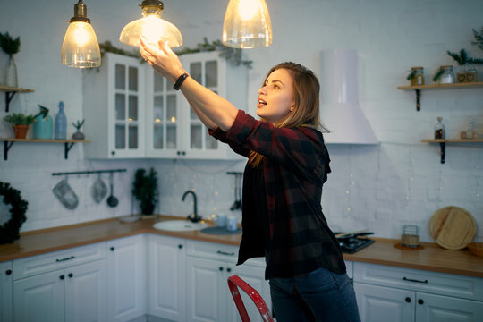 Young woman changing a light bulb at the kitchen