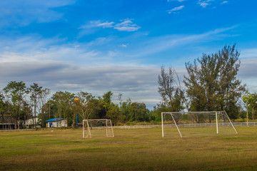 Local football stadium with goal post and blue sky and white clouds background in the rural area. Soccer field in the provincial school with green grass, goal post and blue sky background.