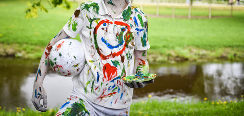 Child dirty in multicolored paint. The concept of colorful fashion and washable clothes. Your design ideas.