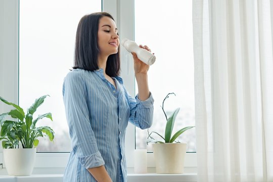 Morning portrait of young smiling woman drinking milk drink yogurt from bottle, woman standing at home in shirt near the window, healthy food eating
