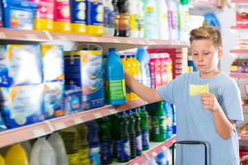 Focused cheerful boy looking at shopping list
