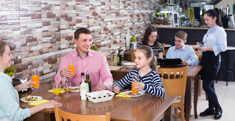 family with teenage children enjoying meal in cafe