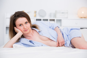 Girl in blue shirt playfully posing and relaxing in bed