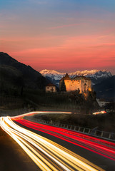 Light Trails on road passing Castle towards Mountains in South Tyrol - sunset/alpine glow