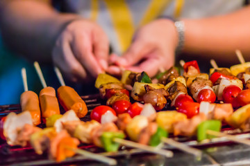 Seafood and beef barbecue (BBQ) skewered on bamboo sticks with pie apple, tomato, onion and chili are grilling on the stove for barbecue party. Barbecue skewers meat kebabs with vegetables at night.