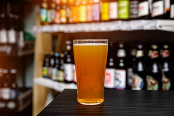 Glass of craft beer at the bar. Assortment of bottles on a blurred background