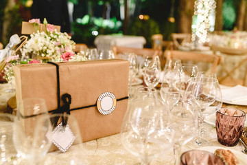 Gift box wrapped in paper and with bow and empty label to include free text, on the elegant table of the reception of a wedding, without anyone.