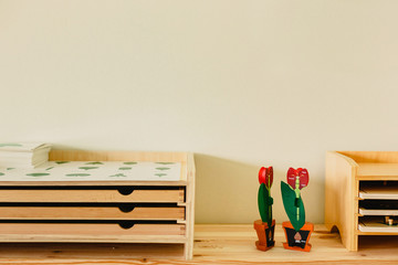 Shelves with wooden educational material in a montessori school.