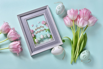 easter flat lay with bunch of pink tulips and greeting card in a frame