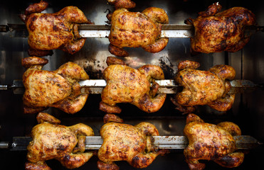 Several hot roasted skewered cooked whole chickens, or rotisserie chicken in Colombia, South America.