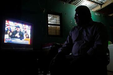 A man watches a TV broadcast of Nicaraguan President Daniel Ortega in Managua, Nicaragua