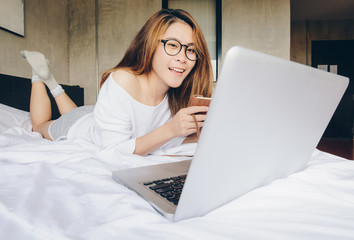 Portrait of pretty Asian woman lying on the bed and working on laptop. Conceptual of woman lifestyle, freelance business.