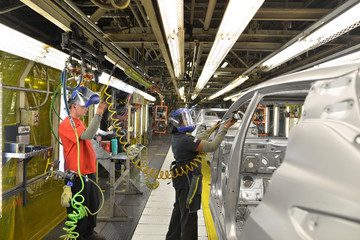 Line workers smooth out the metal along the door frames on the flex line at Nissan Motor Co's automobile manufacturing plant in Smyrna Tennessee