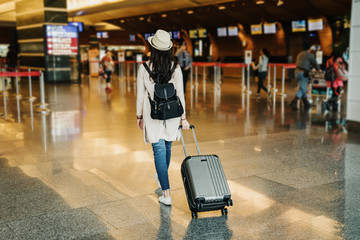 back view of young asian businesswoman in business travel trip drag luggage suitcase walking to lobby. female backpacker in hat going check in to counter airline. passengers in airport.