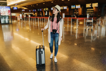 full length of serious young chinese woman is looking for right direction on information board at airport. asian girl traveler standing near suitcase in lobby with check in counter in background.