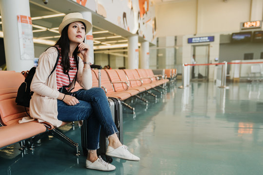 asian travel woman relaxing with luggage suitcase in airport lounge room. young girl arrive early sitting in boarding gate waiting for departure plane flight indoors. bored lady looking outside apron