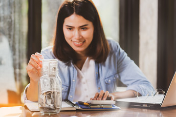 Asia woman counting money and putting banknotes money into the glass bottle with happy.