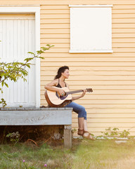 Smiling young woman playing guitar outdoors