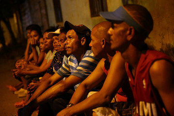 A group of Venezuelans gather for prayers along a street on the outskirts of Cucuta