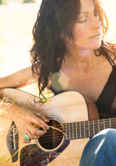 Beautiful, sexy, healthy, creative young woman playing guitar outdoors. Women's natural health and wellness lifestyles.