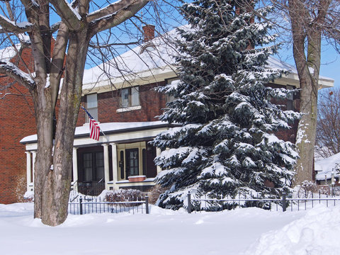 house with large front porch, American flag, and snow covered pine tree