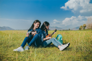 Friendship of Asian teenager women resting outdoor with camera and ukulele her playing music relax.
