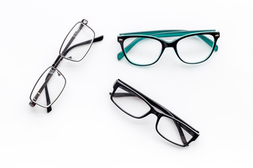 Set of glasses with transparent lenses on white background top view
