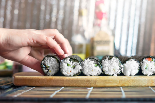 Making Sushi Rolls Workshop. Female Hands Put Rolls On the Wooden Board for Sealing. Kitchenware and Shiny Metal Background.