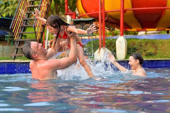 Portrait of happy family having fun in swimming pool in summer