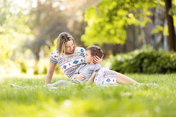 Mother and son sitting on a grass in park