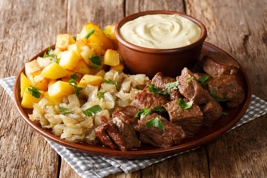 Fried Beef Rydberg served with onions and crisp potatoes with mustard sauce close-up on the table. horizontal