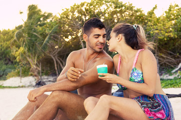 beach lifestyle portrait of young couple sitting on the sand