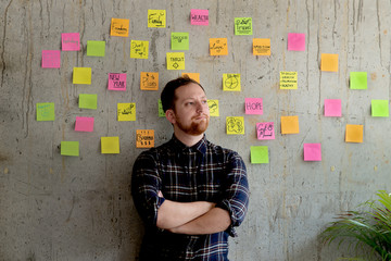 Happy man crossed arm with sticky notes chart on cement wall.  Entrepreneur concept.