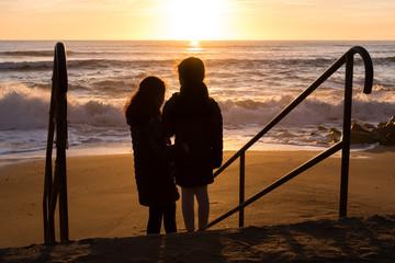 Enfants regardant un coucher de soleil à la mer aux Sables d'Olonne