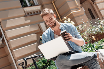 The key to success is action. Young smiling man sitting in the park, holding his laptop and a cup of coffee. His bike stands beside him. Rest, communication and relax concept
