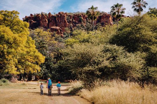 Frau wandert mit Kindern unterhalb des Waterberg Plateaus, Namibia