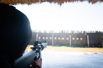 A young girl shooting an air rifle at a target outdoor