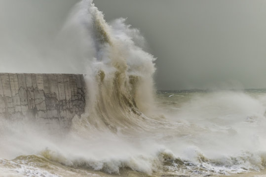 Stunning dangerous high waves crashing over harbor wall during windy Winter storm at Newhaven on English coast