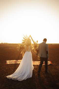 young and beautiful bride and groom enjoy each other. Wedding day in boho style. Sunshine portrait of happy bride and groom outdoor in nature at sunset. Warm summertime.