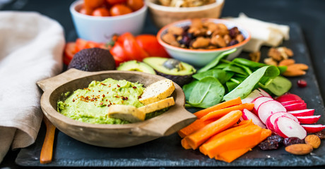 Healthy food selection with guacamole , raw veggies, green leaves spinach, herbs and ingredients, mix of nuts, clean eating, healthy vegan food