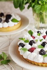 Beautiful freshly made berry meringue tart decorated with mint leaves on plate. Stunning Blackberry meringue pie still life composition. Food photography.
